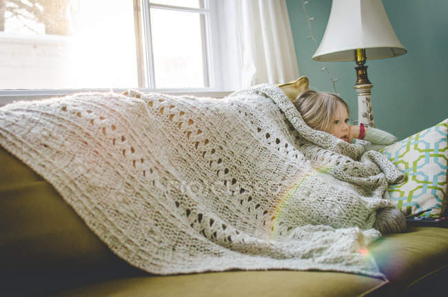 Girl sitting under blanket — Stock Photo