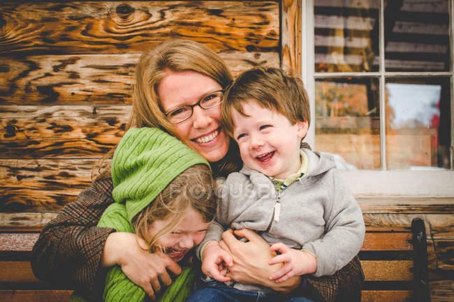 Мать щекотки сына и дочь — стоковое фото
