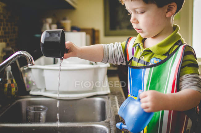 Boy playing with measuring cups and water — Stock Photo
