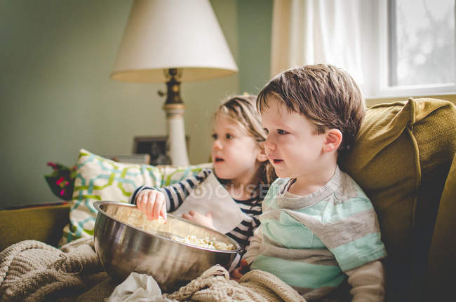 Two children sitting on sofa — Stock Photo