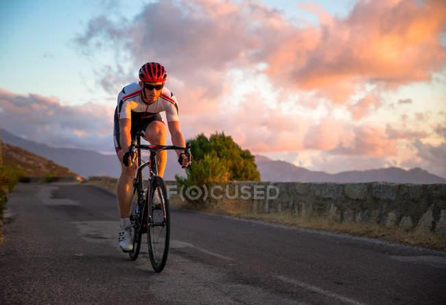 Homem de bicicleta ao pôr do sol — Fotografia de Stock
