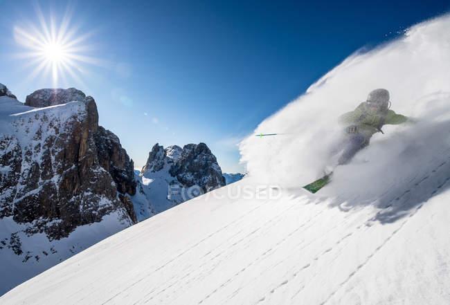 Человек катается на лыжах с трассы — стоковое фото