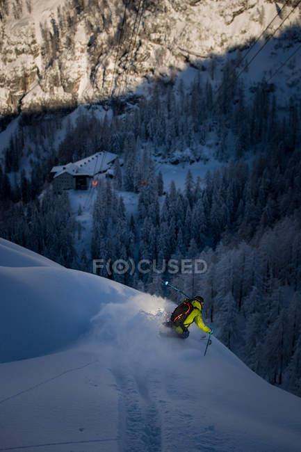 Pó de homem esquiar ao entardecer — Fotografia de Stock