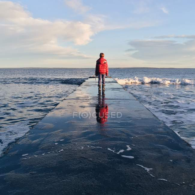 Boy standing on jetty — Stock Photo