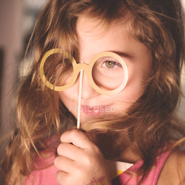 Girl holding party prop glasses on stick — Stock Photo
