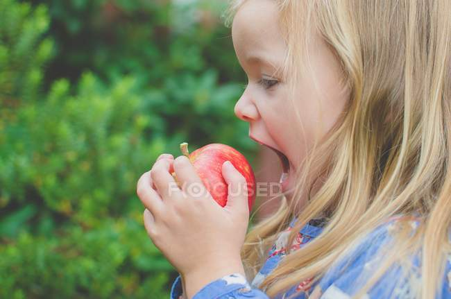 Girl about to take bite out of apple — Stock Photo