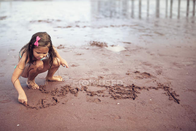 Girl writing on sand — Stock Photo