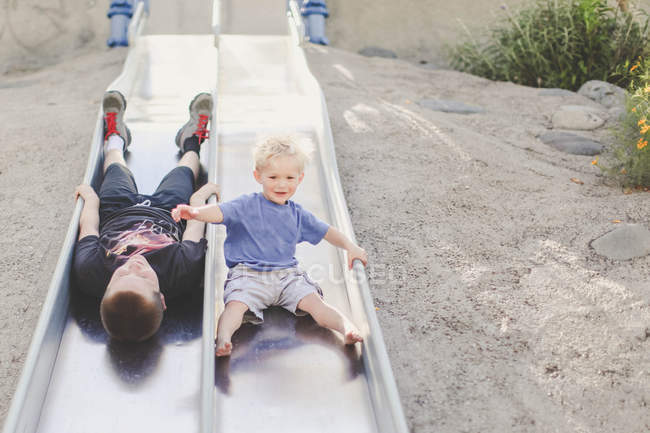 Two boys playing on slide — Stock Photo