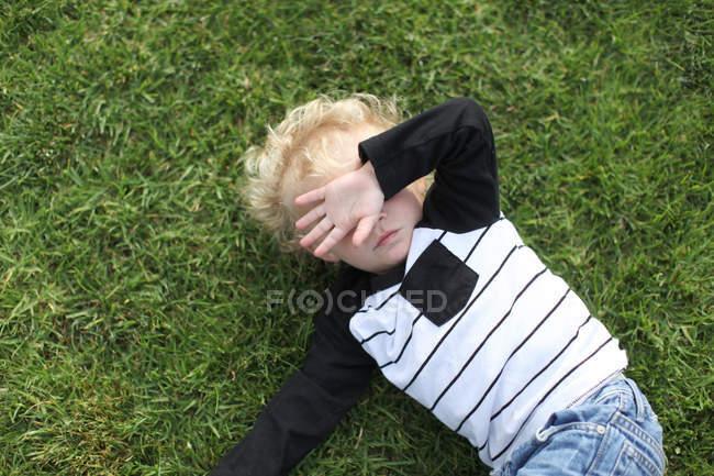 Menino deitado no chão — Fotografia de Stock