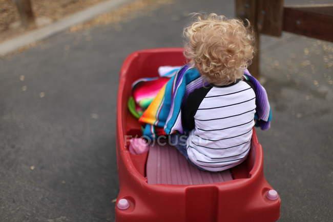 Boy sitting in plastic car — Stock Photo