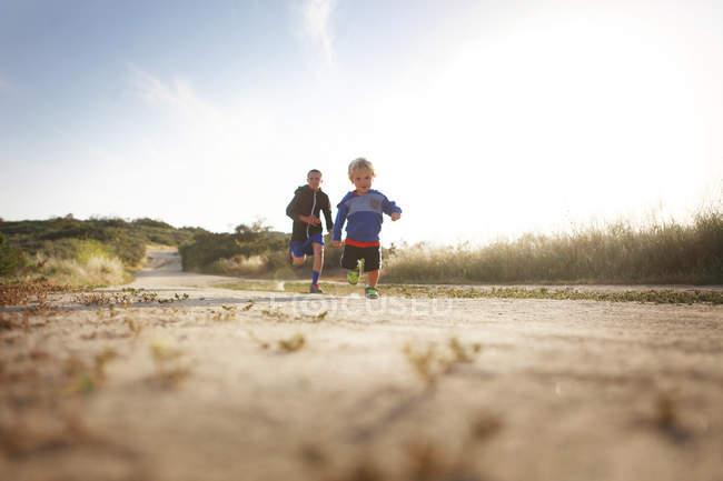 Dos niños corriendo en campo - foto de stock