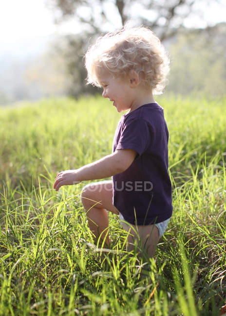 Boy kneeling in grass — Stock Photo