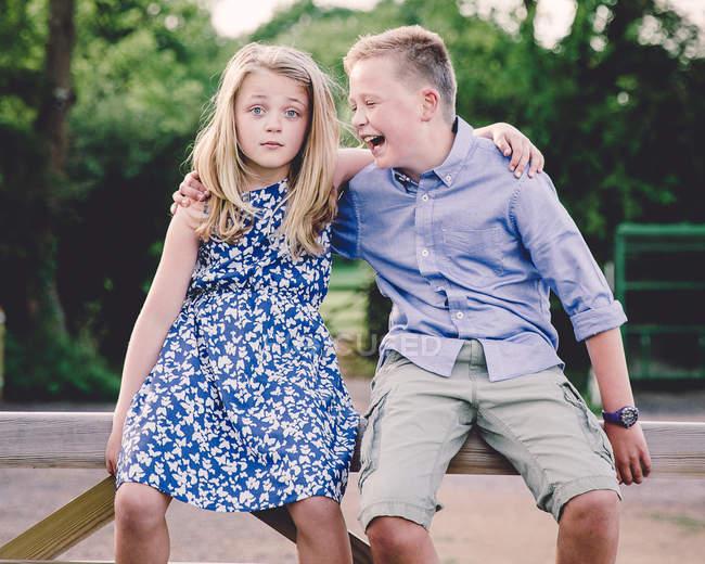 Ragazzo e ragazza seduti su un cancello di legno — Foto stock