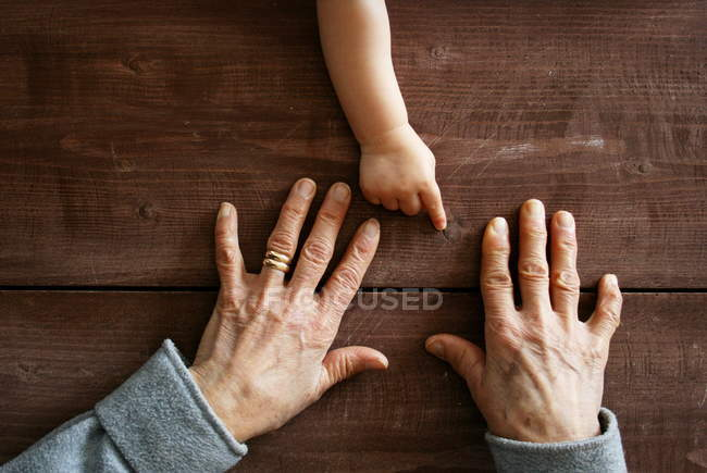 Boy hand pointing at grandmother hands — Stock Photo