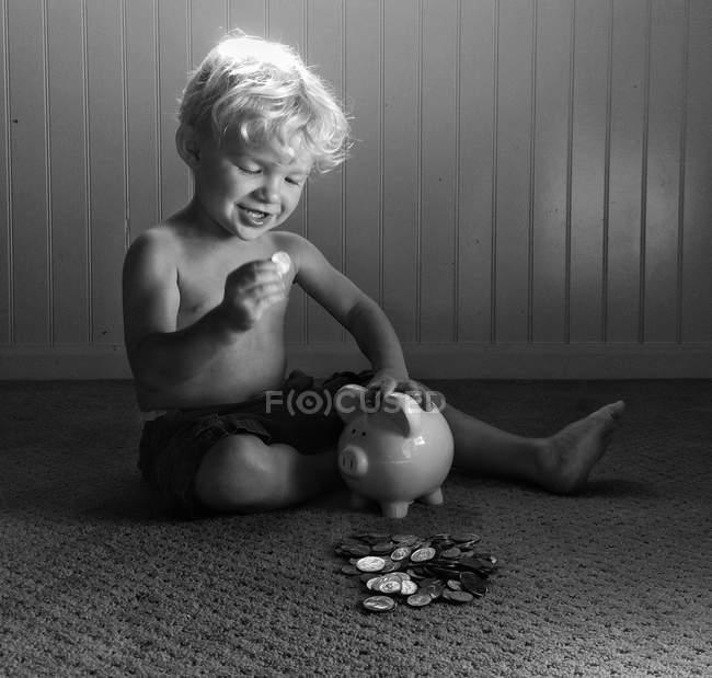 Jungen spielen mit Sparschwein — Stockfoto
