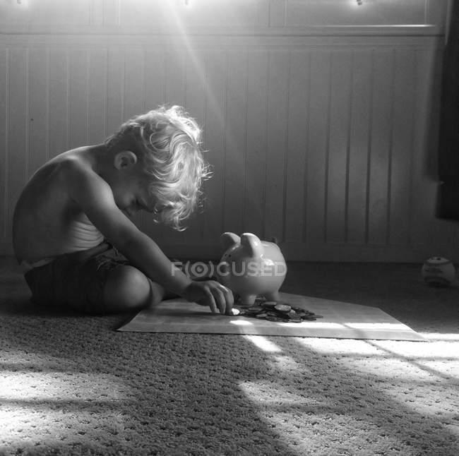 Мальчик играет с копилкой — стоковое фото