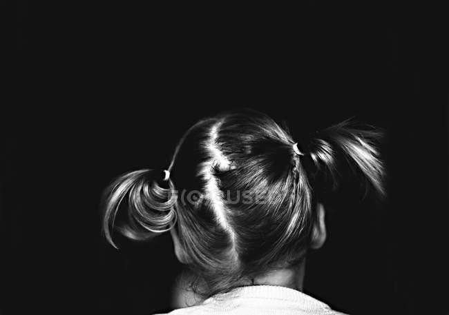 Дівчинка з косичками на чорному — стокове фото