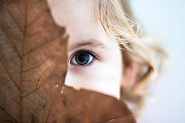 Girl hiding behind leaf — Stock Photo