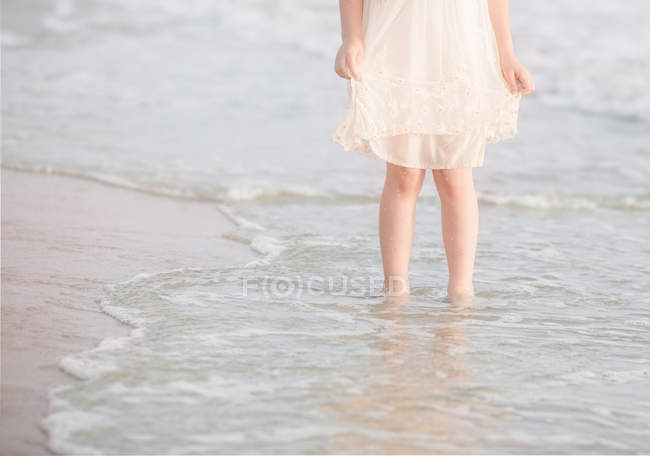 Girl standing in surf at beach — Stock Photo