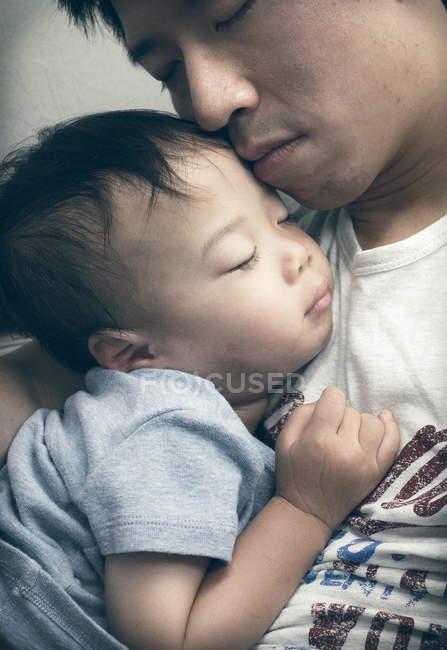 Boy sleeping in father lap — Stock Photo
