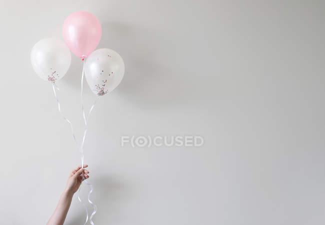 Руки, що тримає повітряні кулі з конфетті — стокове фото