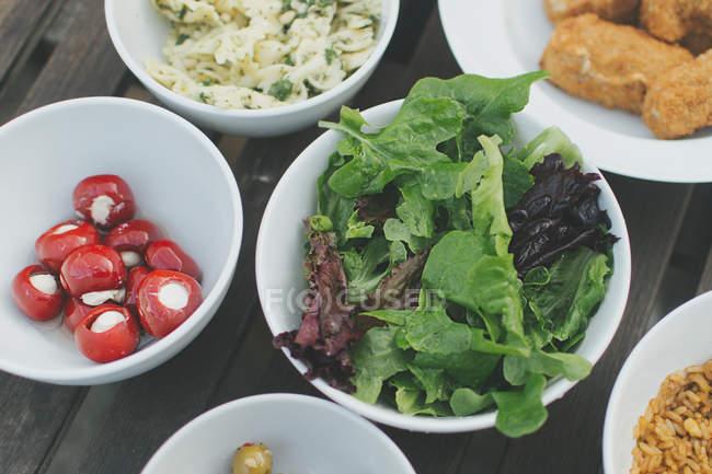 Листья салата, оливки, грецкие орехи в миски — стоковое фото