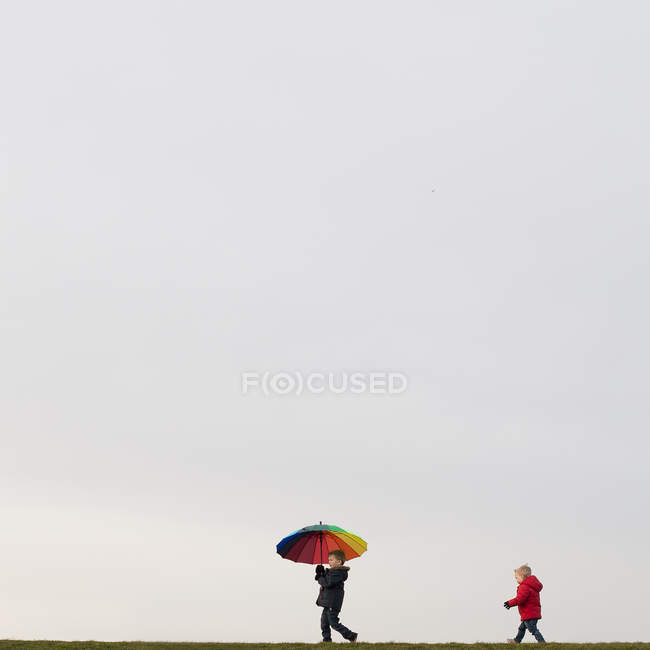 Boys walking, holding umbrella — Stock Photo