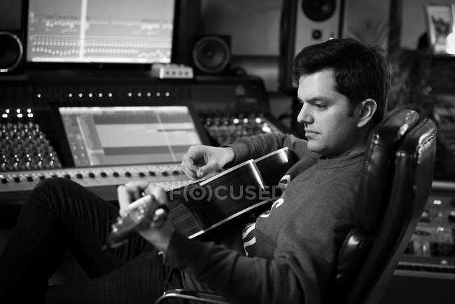 Man playing guitar in recording studio — Stock Photo