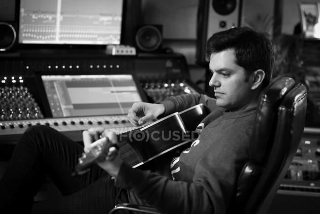 Человек играет на гитаре в студии — стоковое фото