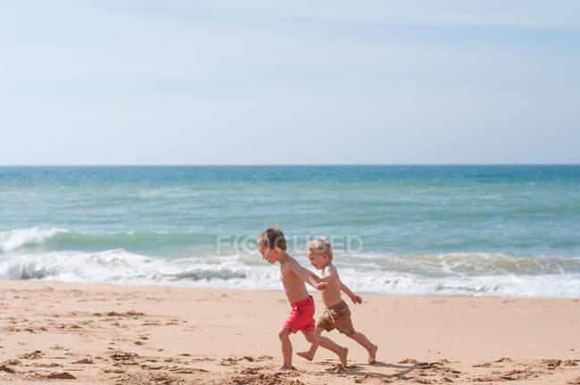 Два мальчика бегут вдоль пляжа — стоковое фото