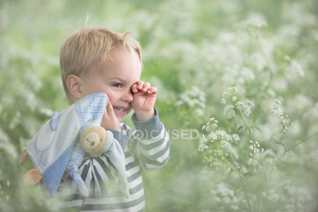 Tired toddler standing in a field — Stock Photo