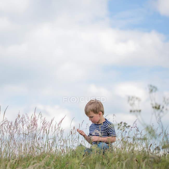 Мальчик сидит в длинной траве — стоковое фото