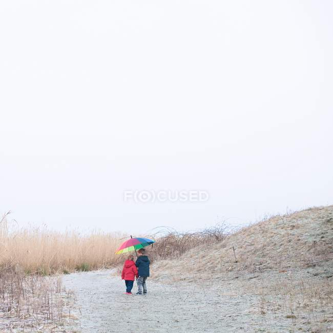Ragazzi che camminano sotto l'ombrello — Foto stock