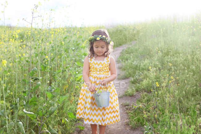 Menina segurando balde cheio de flores — Fotografia de Stock