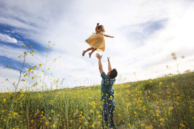 Father throwing daughter in air — Stock Photo