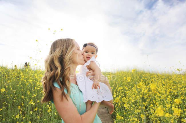 Madre besar bebé niña en el campo - foto de stock