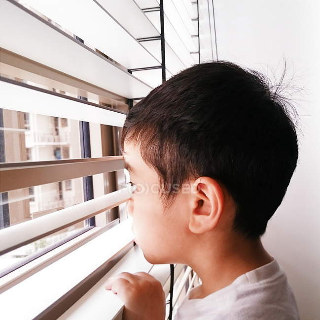 Boy looking through window — Stock Photo