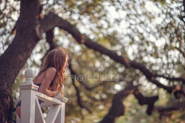 Girl leaning wooden fence — Stock Photo