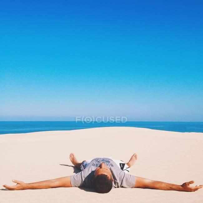 Mann, der auf dem Strand lügt — Stockfoto