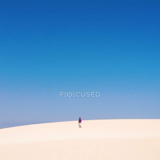 Man walking up sand dune — Stock Photo