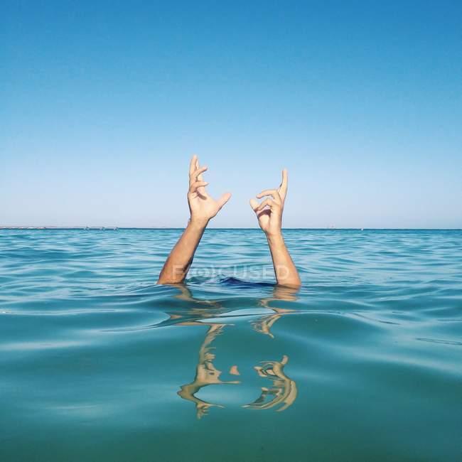 Mãos humanas saindo do mar — Fotografia de Stock