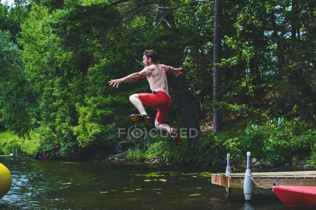 Man jumping off a jetty into lake — Stock Photo