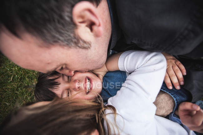 Father, son and daughter tickling each other — Stock Photo