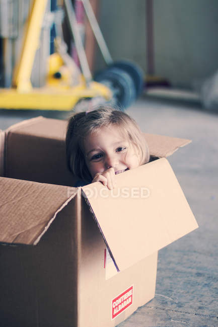 Girl sitting inside cardboard box — Stock Photo