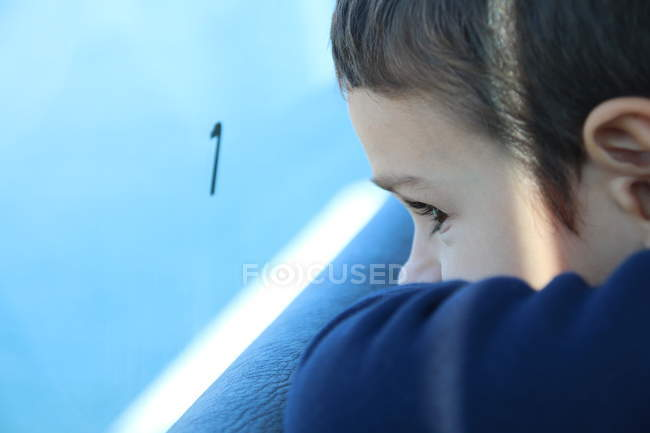 Boy looking out of window — Stock Photo