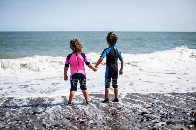 Vue arrière de la fille et du garçon en combinaison — Photo de stock