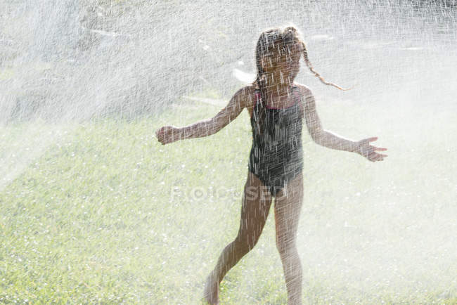 Girl playing in water sprinklers — Stock Photo