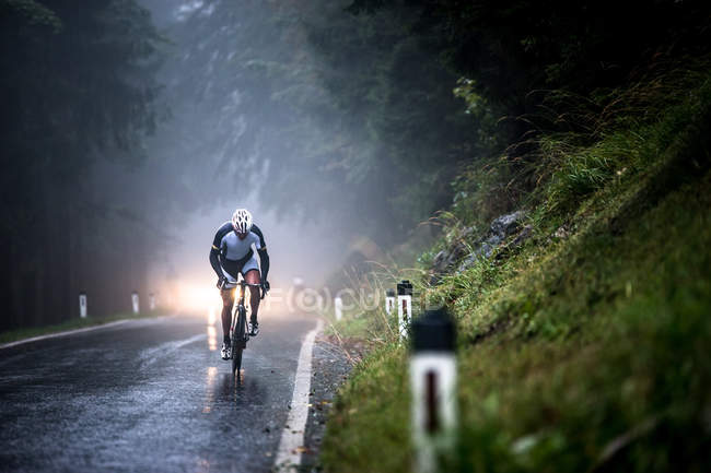 Man cycling on a wet road in rain — Stock Photo