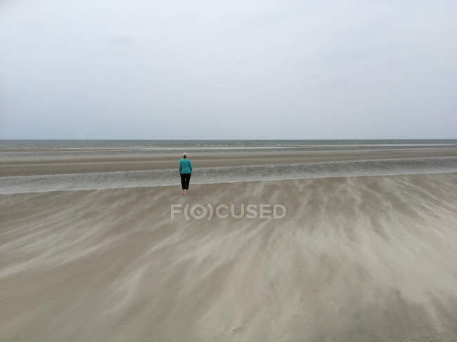 Senior woman standing on beach — Stock Photo
