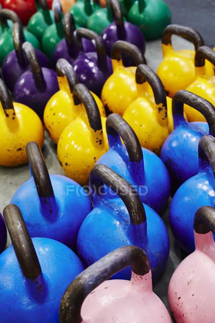 Poids de kettlebells multicolores dans la salle de gym — Photo de stock